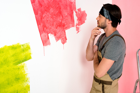 thoughtful young man in working overall looking at half painted wall and holding hand on chin