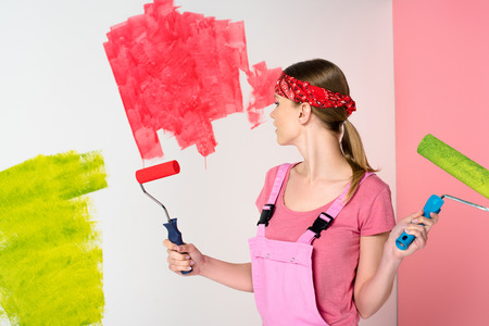 young woman in headband and working overall holding paint rollers in front of painted wall Reklamní fotografie