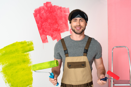 young smiling man in working overall with paint rollers in front of painted wall Reklamní fotografie