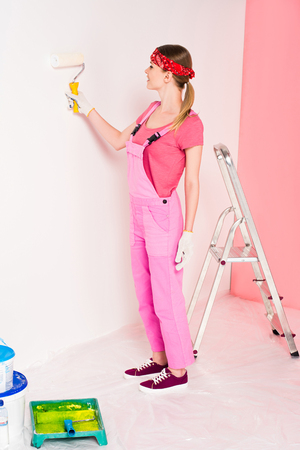 side view of young woman in working overall and headband painting wall by paint roller near ladder