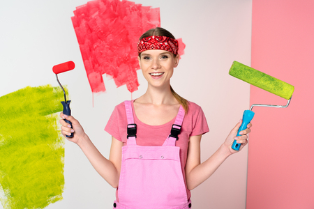 smiling woman in working overall holding paint rollers in front of painted wall