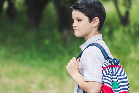 thoughtful schoolboy with backpack looking away at park Foto de archivo