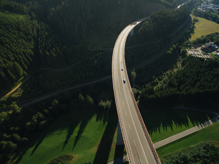 aerial view of cars passing bridge over beautiful green forest Standard-Bild - 106559834