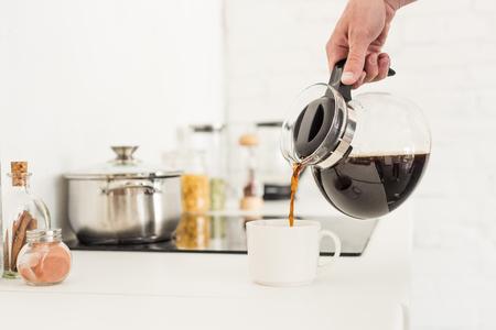 bijgesneden afbeelding van man koffie gieten in beker van koffiezetapparaat op keuken