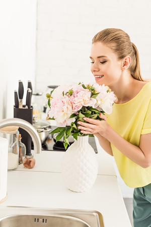 young smiling woman sniffing bouquet of peonies at kitchen