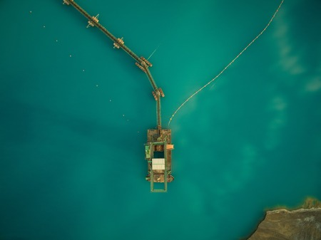 aerial view of sand dredge in blue lake