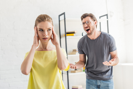 young man screaming at girlfriend while she touching her temples Stock Photo