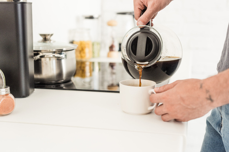 partial view of man pouring coffee into cup from coffee maker at kitchen Stok Fotoğraf - 106560720