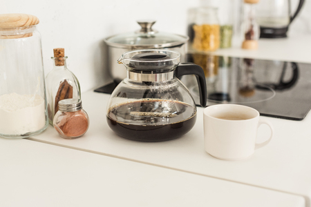 close up view of coffee maker, cup and glass jars near stove on tabletop at kitchen