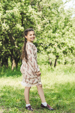 happy child in stylish dress posing in summer park Foto de archivo