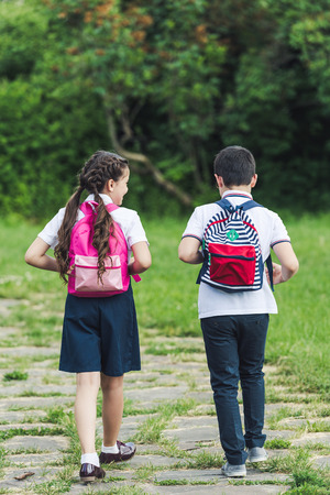 rear view of adorable schoolchildren walking by pathway in park together 写真素材 - 106594274
