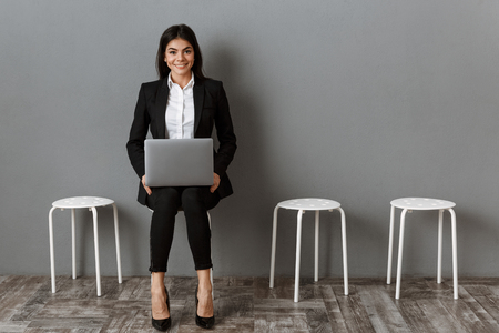 smiling businesswoman in suit with laptop waiting for job interview 免版税图像