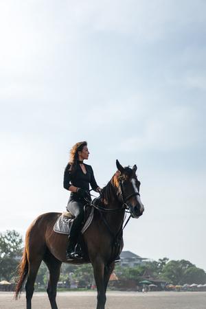 vista di angolo basso della seduta equestre femminile sul cavallo