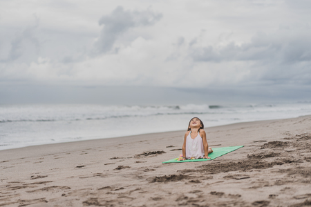 happy little child practicing yoga in Upward-Facing Dog (Urdhva Mukha Svanasana) pose on seashore 写真素材