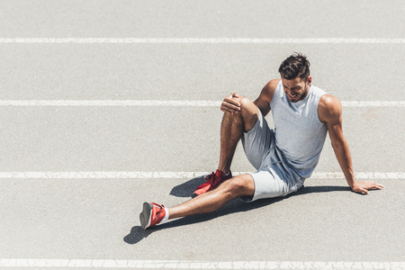fit young jogger with leg injury sitting on running track Archivio Fotografico - 106595888