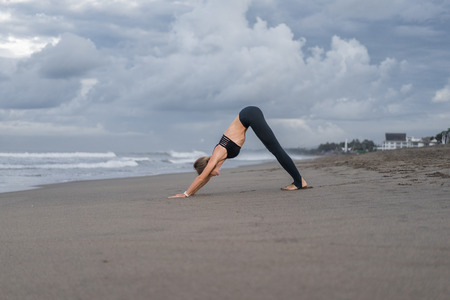 young woman practicing yoga in Downward-Facing Dog pose (Adho Mukha Svanasana) on seashore