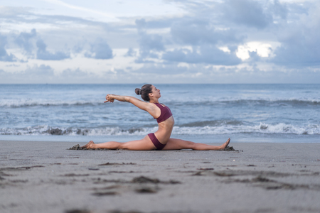 side view of beautiful young woman practicing yoga in front splits pose (Hanumanasana) on seashore Stockfoto