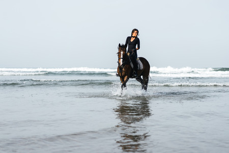 front view of young woman riding horse in wavy water Stock Photo