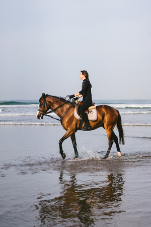 side view of young female equestrian riding horse on sandy beach 版權商用圖片 - 106597050
