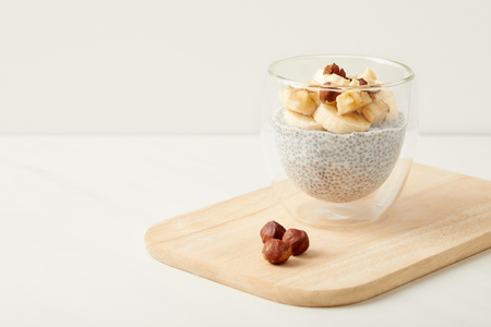 close up view of tasty chia seed pudding with pieces of banana and hazelnuts on wooden cutting board on tabletop 写真素材