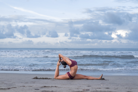 side view of young woman practicing yoga in sss pose on seashore