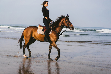side view of young woman riding horse with ocean behind