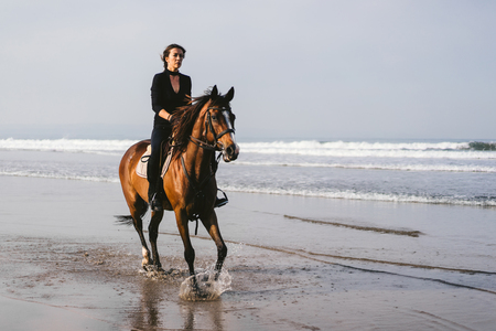 young woman riding horse with wavy ocean behind