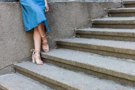 Photo recadrée de femme en jupe en jean et chaussures élégantes debout sur les marches