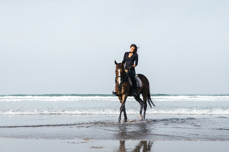 front view of female equestrian riding horse in wavy water
