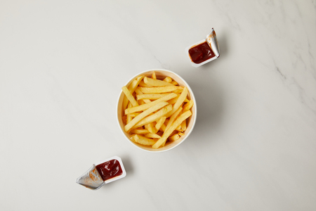 top view of french fries in bowl with containers of ketchup on white Imagens