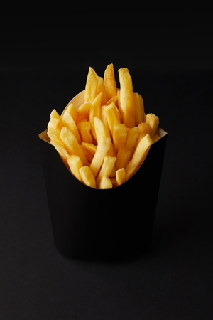 close-up shot of black box of tasty french fries isolated on black isolated on black 免版税图像