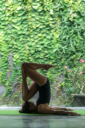 side view of beautiful young woman practicing yoga in entrance into Plow pose (Halasana) in front of wall covered with green leaves