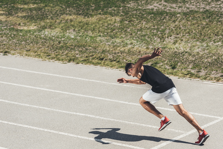 young male sprinter taking off from starting position on running track