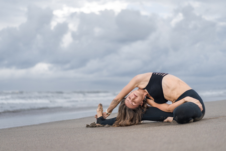 attractive young woman practicing yoga in side bend pose on seashore