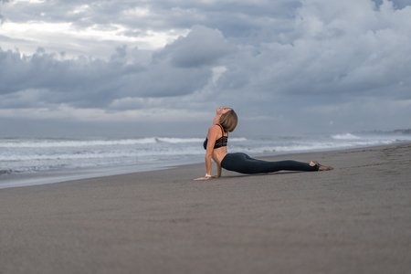 side view of sportive young woman practicing yoga in Upward-Facing Dog pose (Urdhva Mukha Svanasana) on seashore