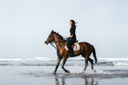 young female equestrian riding horse with ocean behind