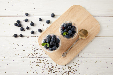 top view of chia puddings with fresh blueberries and mint on wooden cutting board on white surface Stock Photo