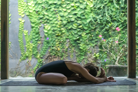 side view of young woman practicing yoga in half hero stretch pose in front of wall covered with green leaves Reklamní fotografie