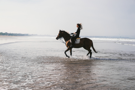 young female equestrian riding horse in water