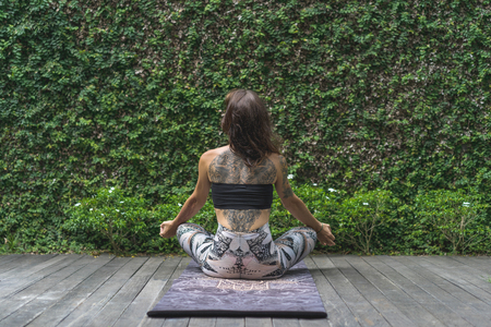rear view of woman practicing yoga in lotus pose in front of wall covered with green leaves Фото со стока