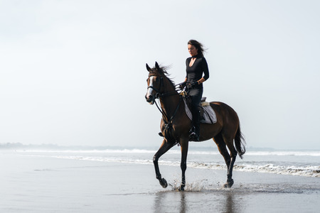 young woman riding horse on sandy beach with ocean behind Archivio Fotografico