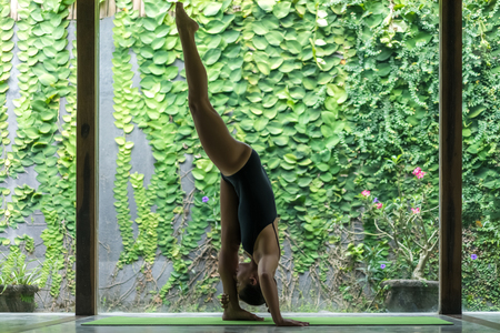 side view of beautiful young woman practicing yoga in Standing Splits pose (Urdhva Prasarita Eka Padasana) in front of wall covered with green leaves