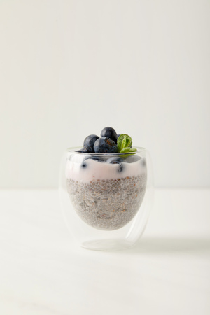 close up view of chia seed pudding with blueberries and mint on white surface