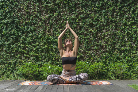 beautiful young woman practicing yoga in lotus pose with raised namaste mudra in front of wall covered with green leaves