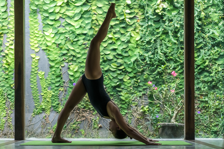 side view of fit young woman practicing yoga in One Legged Downward-Facing Dog pose (Eka Pada Adho Mukha Svanasana) in front of wall covered with green leaves