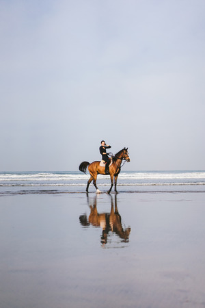 distant view of female equestrian riding horse on beach Zdjęcie Seryjne