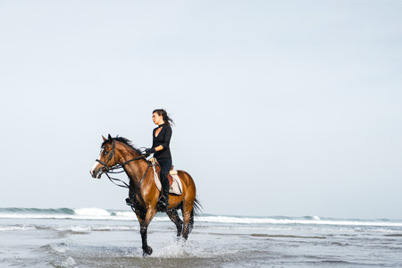 young female equestrian riding horse in wavy water Stock Photo