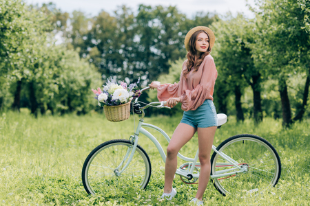 young beautiful woman standing near retro bicycle with wicker basket full of flowers in forest Zdjęcie Seryjne