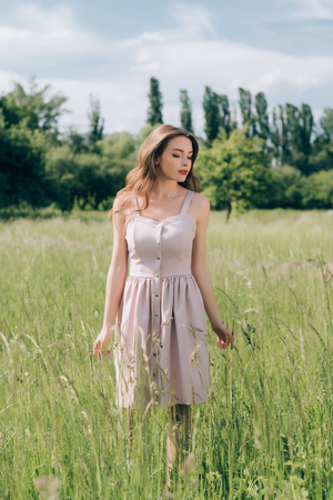 young pensive woman in stylish dress with long hair walking in meadow alone