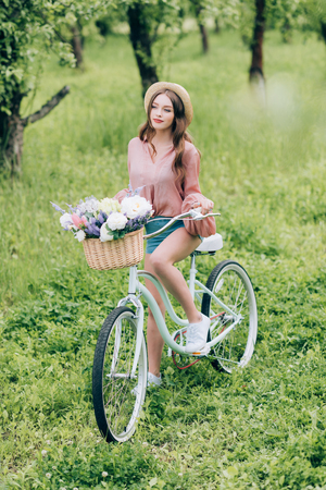 young woman on retro bicycle with wicker basket full of flowers in forest Foto de archivo - 106599192